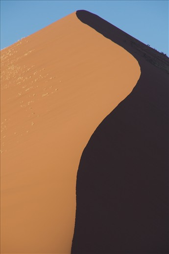 Morning sunrise creating a knife edge that is defined by shadow in the worlds tallest sand dunes of Soussovlei