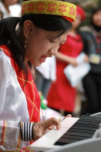 Giang has only 3 fingers on each hand but she can play organ and sing beautifully. In this picture, she is playing organ and singing a song name