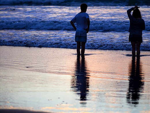 A young couple stand in the wash of the surf watching the sunset.