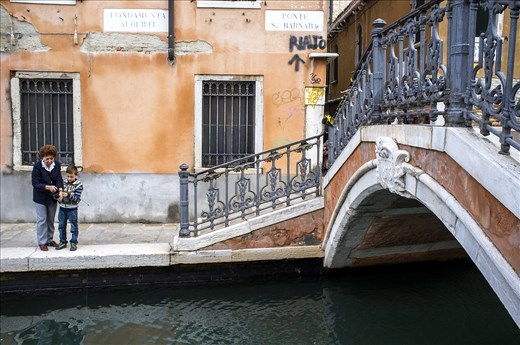 A grandmother helps her grandson fish in the canals of Venice.