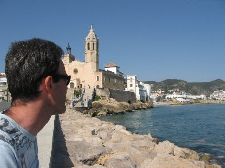 Nigel sitting on the esplanade in Sitges with the church in the background.