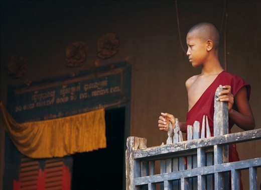 A young monk tied to his village for spiritual belief and religion.
