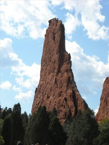 There is a climber at the top of this rock