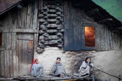 As dusk sets in, women & their family, sit outside waiting for their men to return from work.
