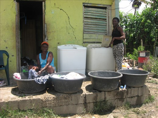 Two women washing clothes by hand next to previously donated  washing machines. The scene seemed odd, and I wondered why they were not using the appliances. I later learned they simply could not, as the machines were not adapted to their living conditions.