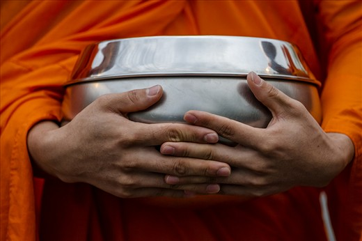 Buddhist monks blesses you as you give them an offering of food in a daily ritual. The bowl holds the goods you give them. In Thailand monks are not vegetarian, because they eat what ever the people give them.