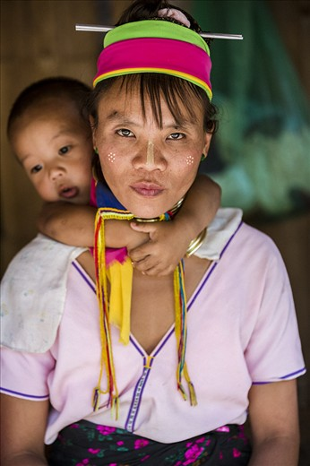 Mother and Son of Karen Long Neck Hill Tribe  The mother is not happy when her son appears from the hut behind her. This is because only the girls wear the long neck rings, and the boys are not wanted in tourist photos...