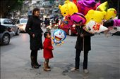 A woman buys her daughter a balloon for