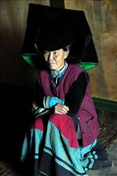 In or out of fashion? Elderly lady of the Yi ethnic group fully clad in traditional costume sitting by the fire place waiting for the family to come back from the fields.: by photogeek, Views[187]