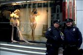 New York, United States of America, two policemen posing and holding a British boy band miniature figure in front of a provocative Victoria's Secret lingerie store window in the center of business and fashion. We live in a plastic world where looks and bank balances determine your value to the society. People are obsessed with fame and celebrities, even the police are there to entertain. Media and businesses create global trends and unrealistic expectations and try to capitalize with them in every turn, anything goes when it comes to marketing. We are slaves of market forces.: by photographeronprogress, Views[272]
