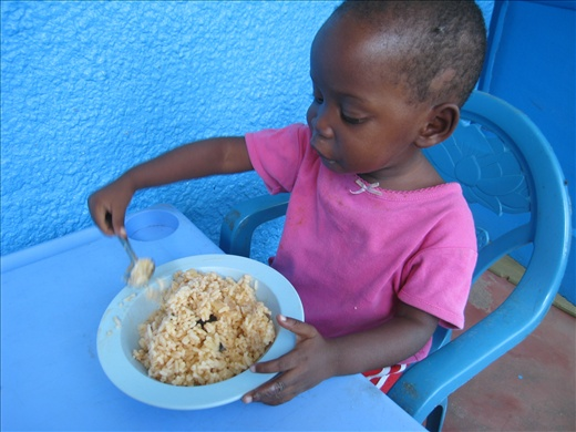 A very precise-eating toddler at the orphanage