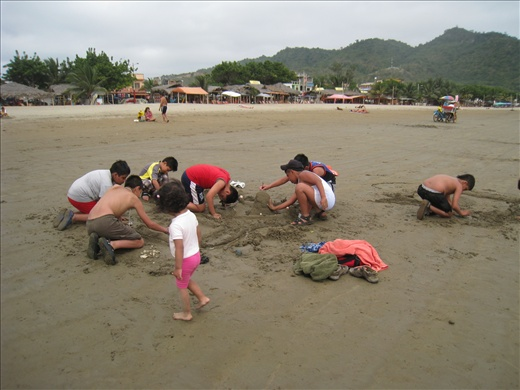 Kids building sand castle on the beach, I enjoy seeing scenes like this compared to kids playing video games.