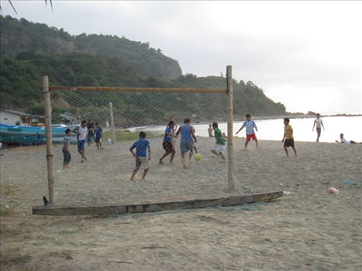 A pick-up game of barefoot football on the beach in the afternoon
