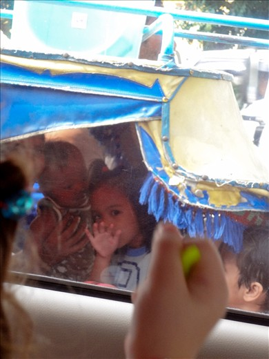 One of the several children all crammed into a tricycle with their parents shares a moment with my 3 year old sister before motoring off into the chaotic haze of local traffic.