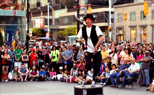 A street performer brings joy to people of all age, sex and color.