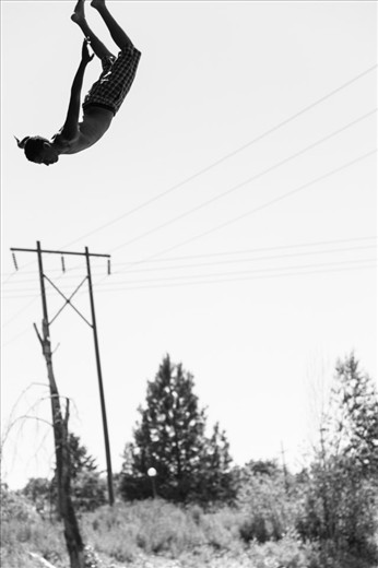 """(3) Missoula is intertwined with several beautiful rivers.  Though famous for its fly fishing, the Clark Fork River that bisects the town draws a constant flow of thrill-seeking bridge jumpers.  This particular jumper looks strikingly serene in spite of the exhilaration that the experience delivers.  He and his friends were visiting students in town for a swimming competition, but it didn't take them long to blend right in with native """"Missoulians"""" at the river."""