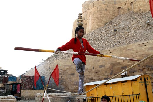 A little girl performing a balancing act on the rope in Jaisailmer,Rajasthan.