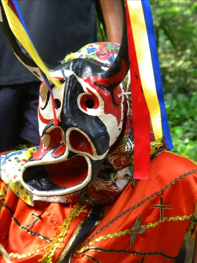 The Devil´s most significant piece of the wardrobe is the mask with exaggerated features and horns with a yellow, blue and red ribbon, and it´s accompanied by a colorful suit similar to those of the Spanish in the seventieth century, garnished with a tail and crosses, a whip in one hand and a maraca in the other. Masks are typically made from clay, wood and paper maché and may vary according to the hierarchy.