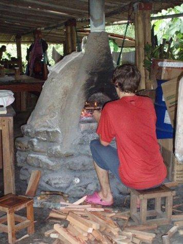 Sam tending the cob oven on baking day.