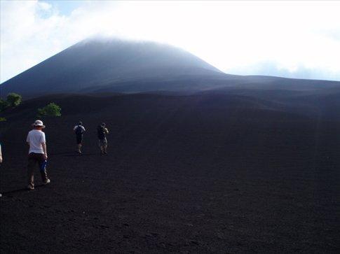 Walking across black sand dunes toward the imposing Cerro Punto volcano