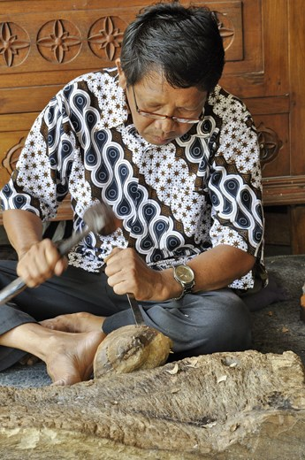 A Balinesian man carves wooden sculptures for tourists to buy. Tour leaders take groups to many destinations like this to watch the workers create wood carvings, jewelry or batik fabrics and make purchases. Incentives are given to the guides if tourist buy items.