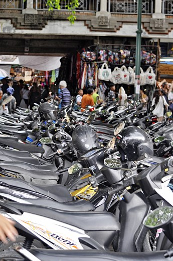 Motorbikes line the street outside of the markets in Ubud. The market place is set up to sell tourists souvenirs. This provides jobs, and monetary gain for the local people in Ubud.