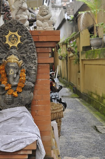 A shrine to a Balinesian god is on a wall near an alley with a motor bike in the background showing how the Western world and tourism has influenced the Balinesian culture.  Now it is a mix between modern ameneties like motor bikes and keeping with the traditional culture in Bali.