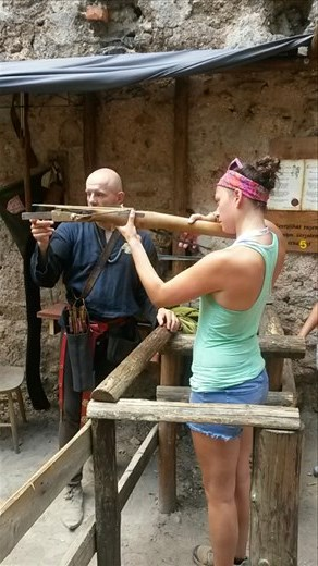 Karmen firing an old-style crossbow at Chojnik Castle