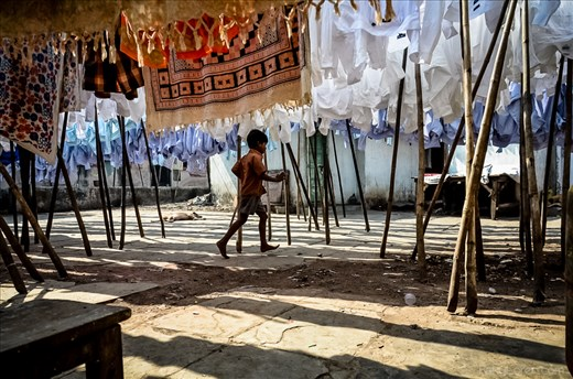 A young boy runs through a courtyard of dwellings within the laundry community.