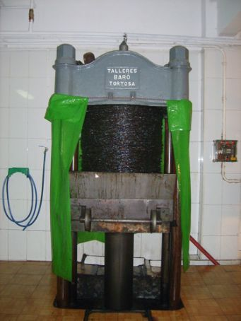Olive press: hydraulic pressure used to push up from bottom, oil forced down through layers of cotton mats (black things)