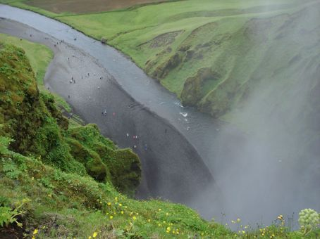 Bird's eye view of people below Skogafoss waterfall