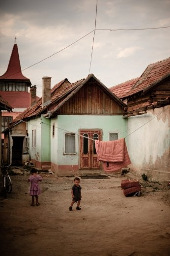 Little children are standing in front of their home in Sfantu Gheorghe, Romania.