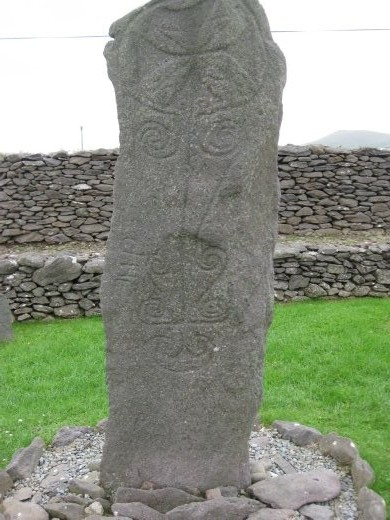 Reask stone pillar with Greek cross and pendant spirals.