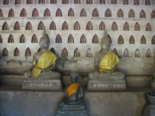 The temple with many small Budha statues in the wall.