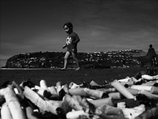 Child playing near piles of cigarette butts