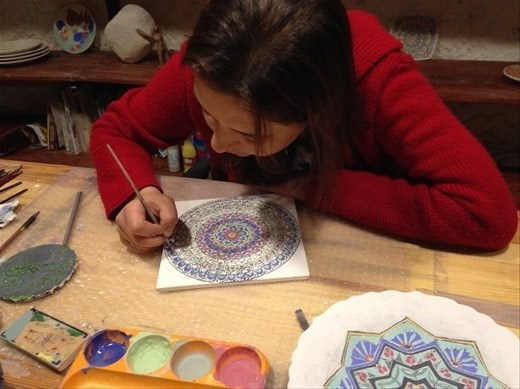 An apprentice hand painting a plate.