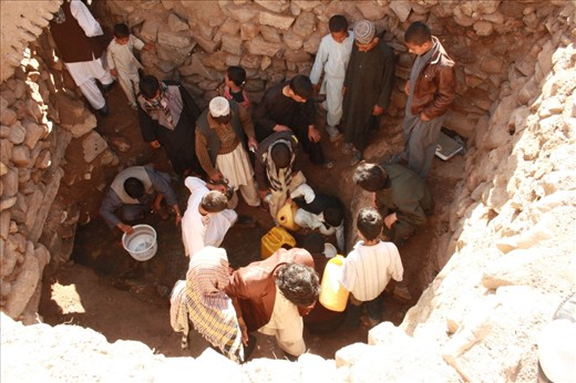 Group of youth are talking water from a natural well which comes from ground