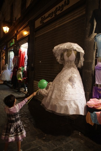 A girl looks in awe at the sight of a glittery wedding dress at Souk el Hamidiyeh