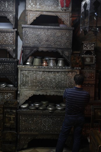 A man contemplates which mother of pearl Damascene chest will be the one