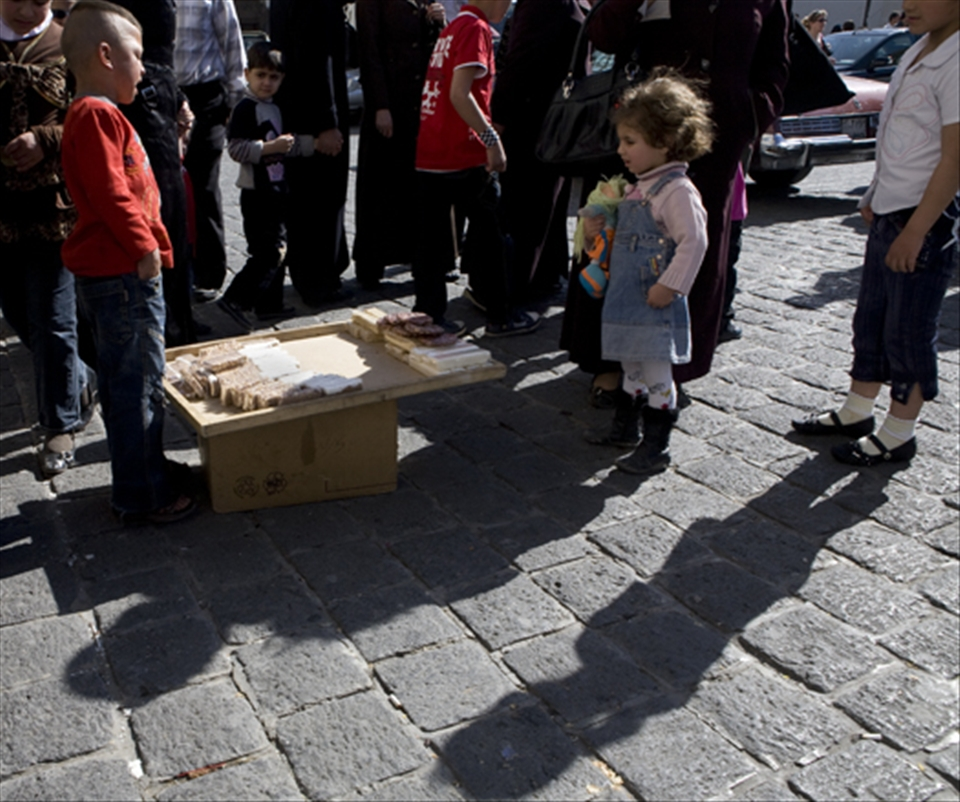 A boy selling Syrian sweets as a girl and bystanders looks on