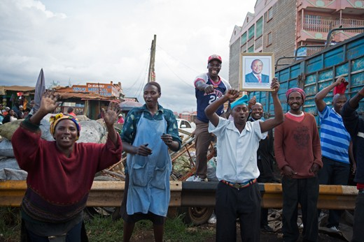 A group of Kenyans celebrate after the  Supreme Court of Kenya rules that the 2013 Presidential Elections here indeed conducted in compliance with the Constitution and were not rigged. A man (fourth from left) holds up a framed portrait of Uhuru Kenyatta, the leader of the winning party, TNA.
