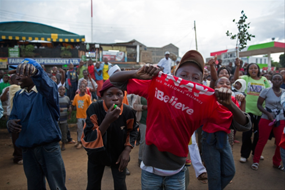 A young Kenyan boy shows his support for the National Alliance Party. It's leader, Uhuru Kenyatta, has just been elected president of Kenya. Other local Kenyans are also celebrating behind him.