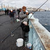 This fisherman has wrapped up warm for a long day holding his line. Accompanied by a deep bucket for his catch his aim is to fill it with migrating fish in the Bosphorus River.: by sarahg, Views[60]