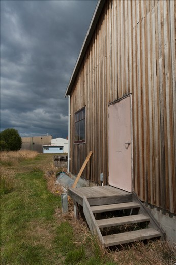On the banks of the quiet Huon River a weathered boat shed stands proud in the face of a building storm.