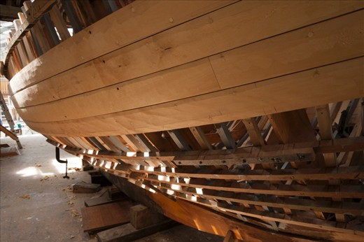 """""""Peggy"""" a 22ft Yacht designed and built by Adrian Dean and named after his wife. At its current state, Huon Pine planks begin to enclose the skeleton of the hull as light leaks through the uncovered areas."""