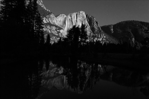 UPPER YOSEMITE FALL: A glassy slow-moving river reflects Upper Yosemite Fall. As night falls in the Park, a lunar moon lights the whole valley, becoming more magical than by day.