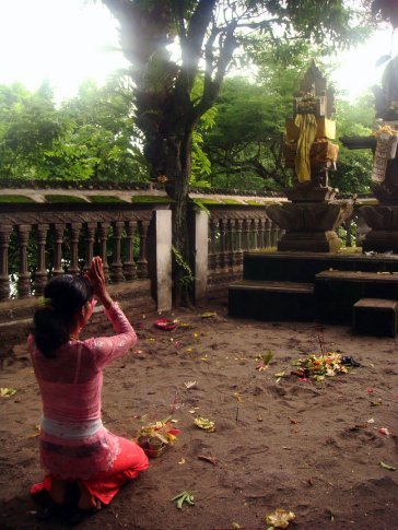 a young lady worshipping at the batu bolong temple