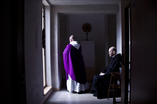 A monk bows his head as the Abbot walks into the oratory