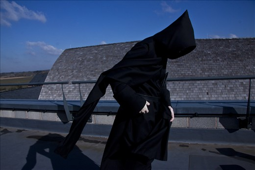 A monk leans into the wind during