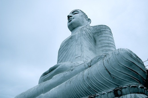 A seated Buddha almosts blends into the ether.
